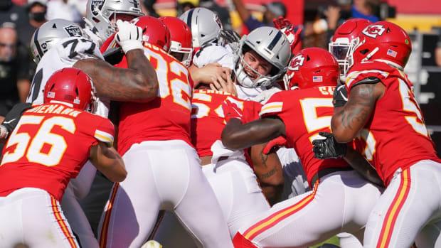 Oct 11, 2020; Kansas City, Missouri, USA; Las Vegas Raiders quarterback Derek Carr (4) runs the ball and is tackled by several Kansas City Chiefs during the game at Arrowhead Stadium. Mandatory Credit: Denny Medley-USA TODAY Sports