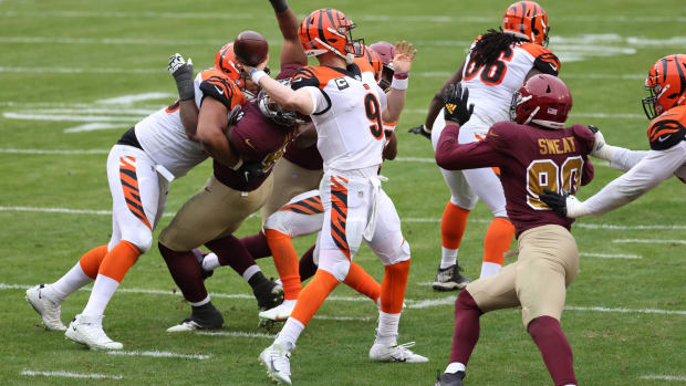 Nov 22, 2020; Landover, Maryland, USA; Cincinnati Bengals quarterback Joe Burrow (9) passes the ball under pressure from Washington Football Team defensive tackle Jonathan Allen (93) in the third quarter at FedExField. Burrow injured his left knee on the play and was carted off the field Mandatory Credit: Geoff Burke-USA TODAY Sports