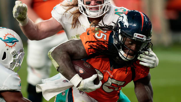 Denver Broncos running back Melvin Gordon III (25) is pulled down by Miami Dolphins linebacker Andrew Van Ginkel (43) in the fourth quarter at Empower Field at Mile High.