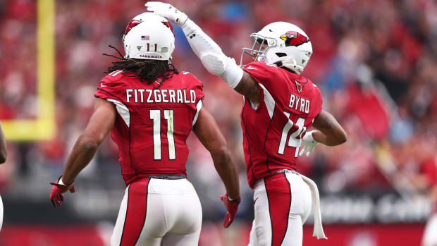 Arizona Cardinals wide receiver Larry Fitzgerald (11) is congratulated by teammate Damiere Byrd after scoring a first quarter touchdown against the Carolina Panthers at State Farm Stadium.