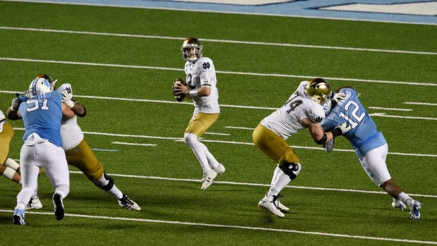 Nov 27, 2020; Chapel Hill, North Carolina, USA; Notre Dame Fighting Irish quarterback Ian Book (12) looks to pass as North Carolina Tar Heels defensive lineman Raymond Vohasek (51) and linebacker Tomon Fox (12) pressure in the fourth quarter at Kenan Memorial Stadium.