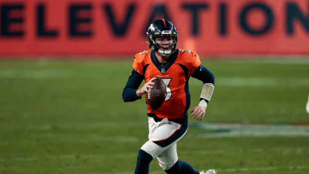 Nov 22, 2020; Denver, Colorado, USA; Denver Broncos quarterback Drew Lock (3) scrambles with the ball against the Miami Dolphins in the fourth quarter at Empower Field at Mile High.