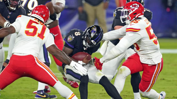 Sep 28, 2020; Baltimore, Maryland, USA; Baltimore Ravens quarterback Lamar Jackson (8) pressured in the first quarter by Kansas City Chiefs defensive ends Mike Danna (51) and Frank Clark (55) at M&T Bank Stadium. Mandatory Credit: Mitch Stringer-USA TODAY Sports