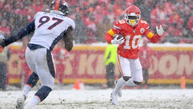 Kansas City Chiefs wide receiver Tyreek Hill (10) runs the ball as Denver Broncos linebacker Jeremiah Attaochu (97) defends during the first half at Arrowhead Stadium.