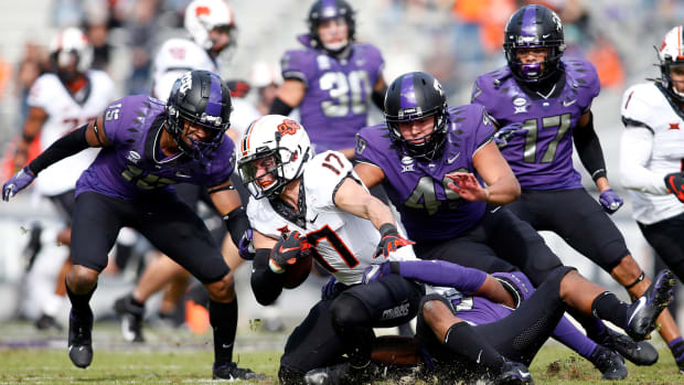 Dec 5, 2020; Fort Worth, Texas, USA; Oklahoma State Cowboys wide receiver Dillon Stoner (17) is tackled by the TCU Horned Frogs defense in the second quarter at Amon G. Carter Stadium.