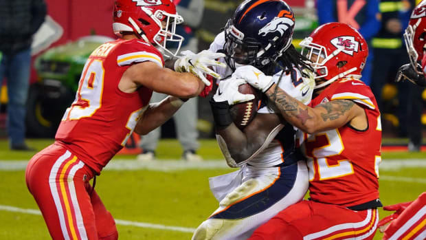 Denver Broncos running back Melvin Gordon (C) is tackled by Kansas City Chiefs free safety Daniel Sorensen (L) and strong safety Tyrann Mathieu (R) during the first half at Arrowhead Stadium.