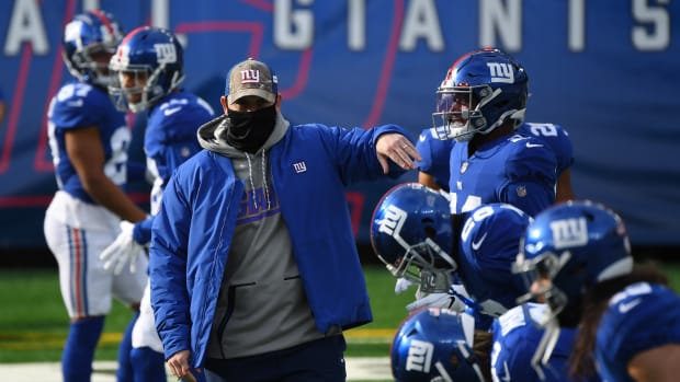 Dec 13, 2020; East Rutherford, New Jersey, USA; New York Giants head coach Joe Judge (left) greets players as they warm up before a game against the Arizona Cardinals at MetLife Stadium.