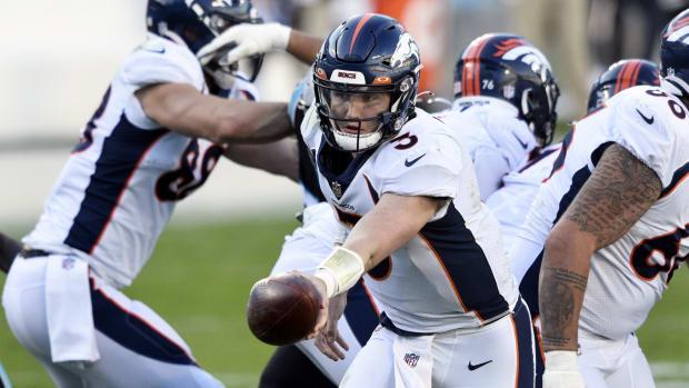 Denver Broncos quarterback Drew Lock (3) hands the ball off in the fourth quarter at Bank of America Stadium.