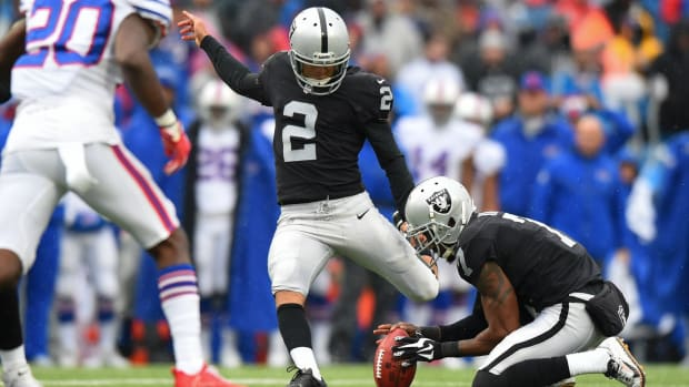 Oakland Raiders kicker Giorgio Tavecchio (2) kicks an extra-point from the hold of punter Marquette King (7) against the Buffalo Bills during the first quarter at New Era Field.
