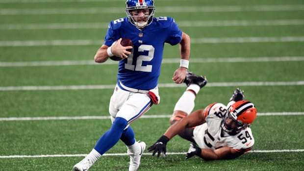 New York Giants quarterback Colt McCoy (12) breaks a tackle by Cleveland Browns defensive end Olivier Vernon (54) during a game at MetLife Stadium on Sunday, December 20, 2020, in East Rutherford.