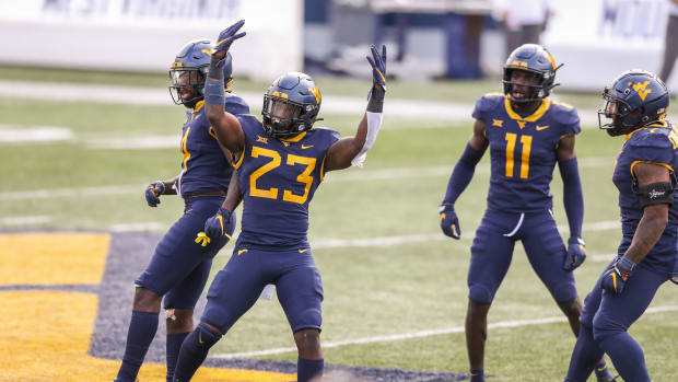 Oct 3, 2020; Morgantown, West Virginia, USA; West Virginia Mountaineers linebacker Tykee Smith (23) celebrates with teammates after intercepting a pass from Baylor Bears quarterback Charlie Brewer (5) during the second overtime at Mountaineer Field at Milan Puskar Stadium.