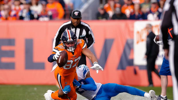 Denver Broncos tight end Noah Fant (87) reaches for a first down as he is pulled down by Detroit Lions cornerback Rashaan Melvin (29) in the first quarter at Empower Field at Mile High.
