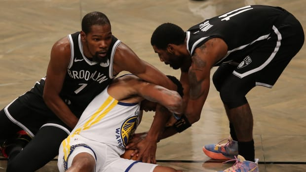 Golden State Warriors shooting guard Kent Bazemore fights for a loose ball against Brooklyn Nets small forward Kevin Durant and point guard Kyrie Irving during the first quarter at Barclays Center.
