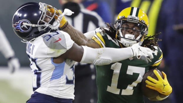 Green Bay Packers wide receiver Davante Adams (17) stiff arms Tennessee Titans free safety Desmond King (33) on a long reception and run in the fourth quarter during their football game Sunday, December 27, 2020, at Lambeau Field in Green Bay, Wis.