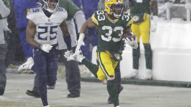 Green Bay Packers running back Aaron Jones (33) runs for a long gain against Tennessee Titans cornerback Adoree' Jackson (25) in the third quarter during their football game Sunday, December 27, 2020, at Lambeau Field in Green Bay, Wis.