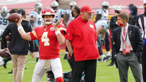 Nov 8, 2020; Kansas City, Missouri, USA; Kansas City Chiefs quarterback Chad Henne (4) warms up while head coach Andy Reid talks with chairman Clark Hunt before the game against the Carolina Panthers at Arrowhead Stadium. Mandatory Credit: Denny Medley-USA TODAY Sports