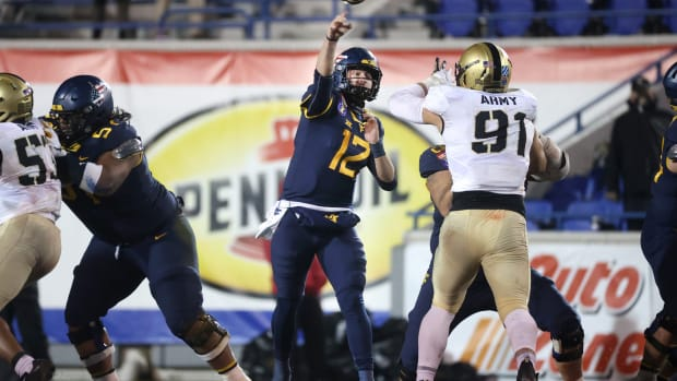 West Virginia Mountaineers quarterback Austin Kendall throws the ball against the Army Black Knights during the AutoZone Liberty Bowl in Memphis, Tenn.