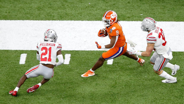 Jan 1, 2021; New Orleans, LA, USA; Clemson Tigers running back Travis Etienne (9) runs with the ball while pursued by Ohio State Buckeyes cornerback Marcus Williamson (21) and linebacker Tuf Borland (32) during the first quarter at Mercedes-Benz Superdome.