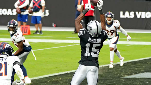 Las Vegas Raiders wide receiver Nelson Agholor (15) attempts to make a catch in front of Denver Broncos cornerback A.J. Bouye (21) during the first half at Allegiant Stadium.