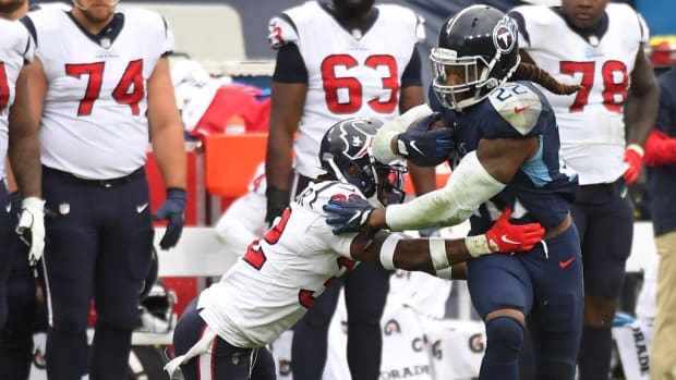 Tennessee Titans running back Derrick Henry (22) fights off a tackle attempt from Houston Texans cornerback Lonnie Johnson (32) in overtime at Nissan Stadium.