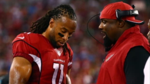 Arizona Cardinals wide receiver Larry Fitzgerald (11) talks with defensive line coach Brentson Buckner against the San Diego Chargers at University of Phoenix Stadium.