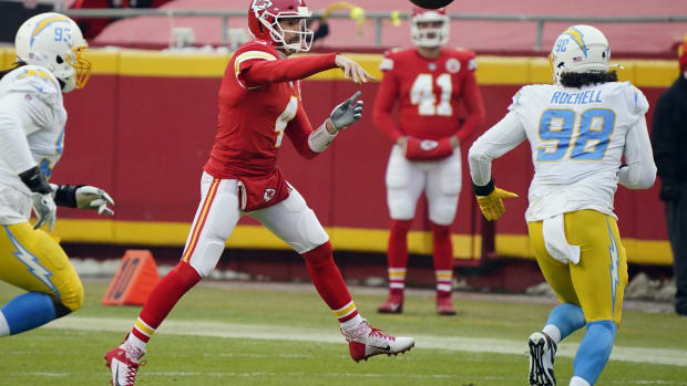 Jan 3, 2021; Kansas City, Missouri, USA; Kansas City Chiefs quarterback Chad Henne (4) throws a pass on the run against Los Angeles Chargers defensive tackle Justin Jones (93) and defensive end Isaac Rochell (98) during the first half at Arrowhead Stadium. Mandatory Credit: Jay Biggerstaff-USA TODAY Sports