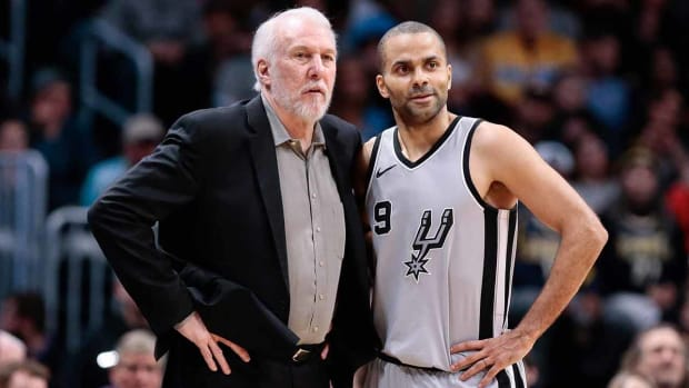 Tony Parker stands with Spurs coach Gregg Popovich.