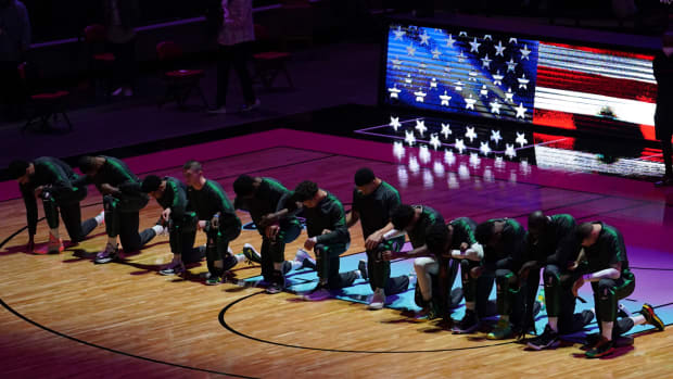 Boston Celtics players kneel during the playing of the national anthem prior to the game against the Miami Heat