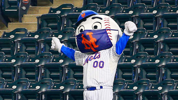 Mr. Met wearing a face mask with his hands raised in triumph