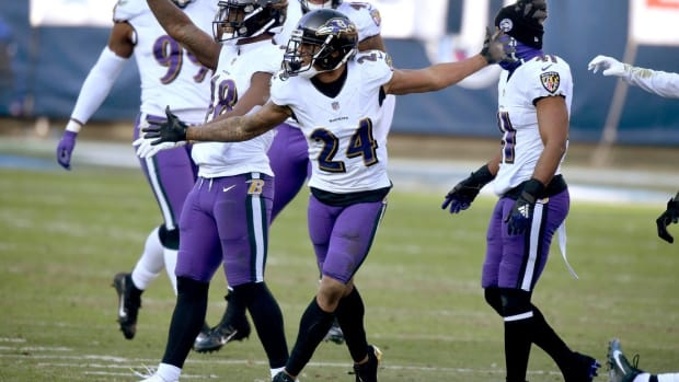Baltimore Ravens cornerback Marcus Peters (24) and his teammates stomp on the Titans logo after Peters picked up an interception to seal their win over the Tennessee Titans in Nashville on January 10, 2021.
