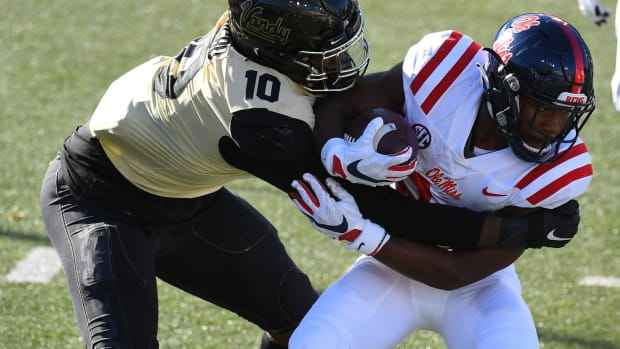 Oct 31, 2020; Nashville, Tennessee, USA; Mississippi Rebels running back Snoop Conner (right) is stopped in the backfield by Vanderbilt Commodores defensive lineman Dayo Odeyingbo (10) during the first half at Vanderbilt Stadium.