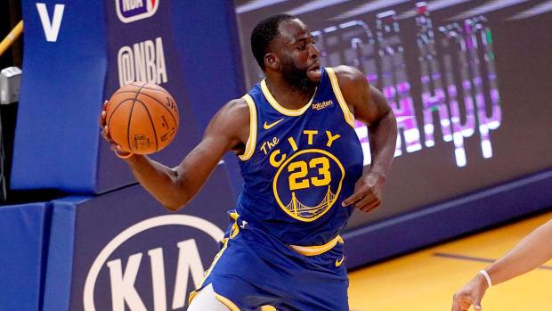 Warriors forward Draymond Green holds a basketball.