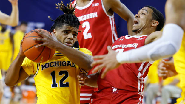 Jan 12, 2021; Ann Arbor, Michigan, USA; Michigan Wolverines guard Mike Smith (12) drives against Wisconsin Badgers guard D'Mitrik Trice (0) in the first half at Crisler Center.