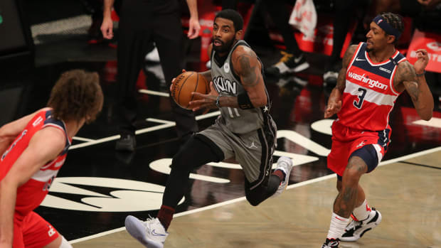 Brooklyn Nets point guard Kyrie Irving (11) drives to the basket against Washington Wizards center Robin Lopez (15) and shooting guard Bradley Beal (3) during the second quarter at Barclays Center.