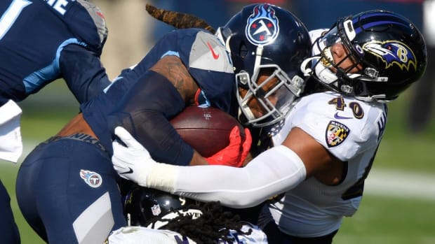 Tennessee Titans running back Derrick Henry (22) is tackled by Baltimore Ravens outside linebacker Pernell McPhee (90) and inside linebacker Malik Harrison (40) during the Tennessee Titans game against the Baltimore Ravens in Nashville on January 10, 2021.
