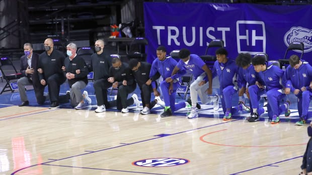 Kentucky Wildcats coaches and players kneel during the national anthem prior to a game against the Florida Gators on Jan. 9, 2021.