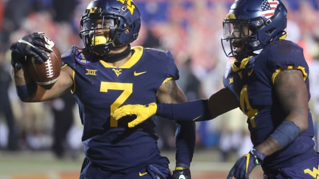 West Virginia Mountaineers linebacker Josh Chandler-Semedo, left, celebrates his game-ending interception against the Army Black Knights in the AutoZone Liberty Bowl in Memphis, Tenn. on Thursday, Dec. 31, 2020