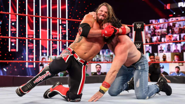 WWE's AJ Styles with Elias in a headlock