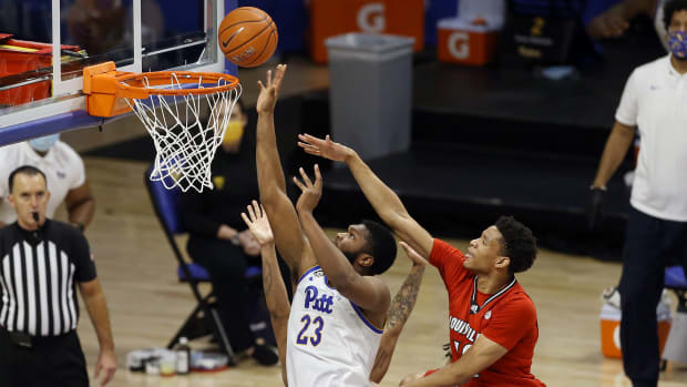 Dec 22, 2020; Pittsburgh, Pennsylvania, USA; Pittsburgh Panthers forward John Hugley (23) shoots against Louisville Cardinals forward J.J. Traynor (right) during the second half at the Petersen Events Center.