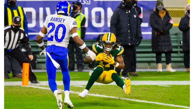 Jan 16, 2021; Green Bay, Wisconsin, USA; Green Bay Packers wide receiver Davante Adams (17) catches a touchdown pass against Los Angeles Rams cornerback Jalen Ramsey (20) in the first half of the NFC Divisional Round at Lambeau Field.