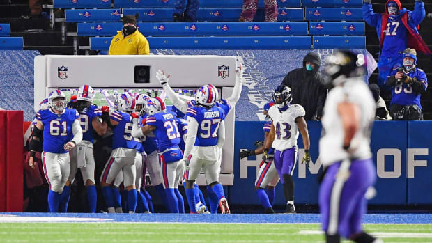 Buffalo Bills cornerback Taron Johnson (24) celebrates with teammates after scoring on an interception against the Baltimore Ravens during the second half of an AFC Divisional Round playoff game at Bills Stadium.
