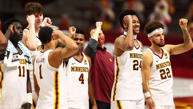 Minnesota basketball players celebrate a win over Michigan