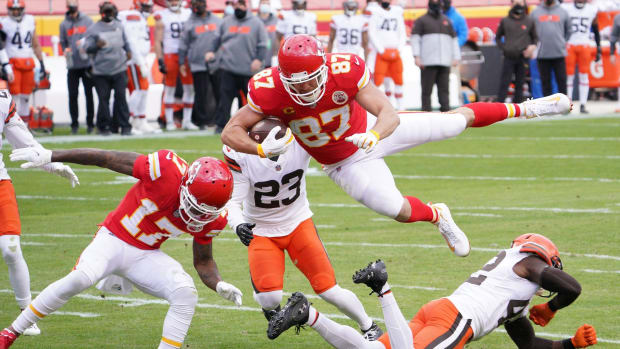 Jan 17, 2021; Kansas City, Missouri, USA; Kansas City Chiefs tight end Travis Kelce (87) leaps over Cleveland Browns strong safety Karl Joseph (42) to score a touchdown during the first half in the AFC Divisional Round playoff game at Arrowhead Stadium. Mandatory Credit: Denny Medley-USA TODAY Sports