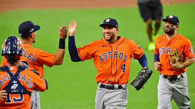 Oct 16, 2020; San Diego, California, USA; Houston Astros center fielder George Springer (4) high fives designated hitter Michael Brantley (23) after their win over the Tampa Bay Rays with teammates after game six of the 2020 ALCS at Petco Park. The Houston Astros won 7-4.