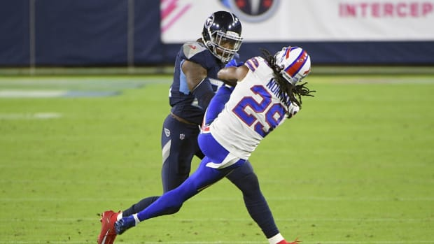 Tennessee Titans running back Derrick Henry (22) throws Buffalo Bills cornerback Josh Norman (29) to the side from a stiff arm during the first half at Nissan Stadium.