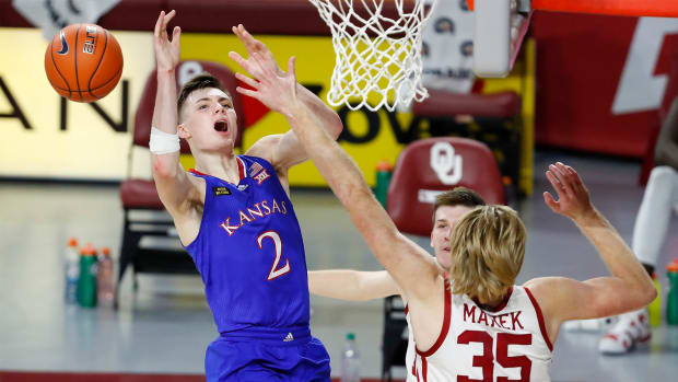 Jan 23, 2021; Norman, Oklahoma, USA; Kansas Jayhawks guard Christian Braun (2) looses control of the ball as Oklahoma Sooners forward Brady Manek (35) defends him during the first half at Lloyd Noble Center.