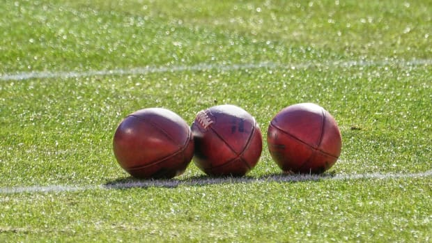 Three footballs on a field