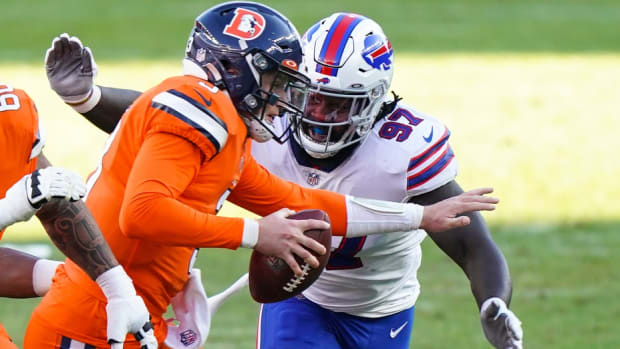 Broncos quarterback Drew Lock (3) is tackled by Buffalo Bills defensive end Mario Addison (97) during the first quarter at Empower Field at Mile High.