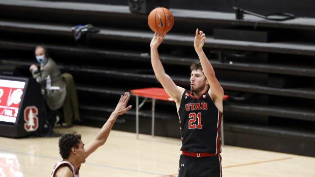 Feb 13, 2021; Stanford, California, USA; Utah Utes forward Riley Battin (21) makes a three point basket over Stanford Cardinal forward Oscar da Silva (13) during the second half at Maples Pavilion.