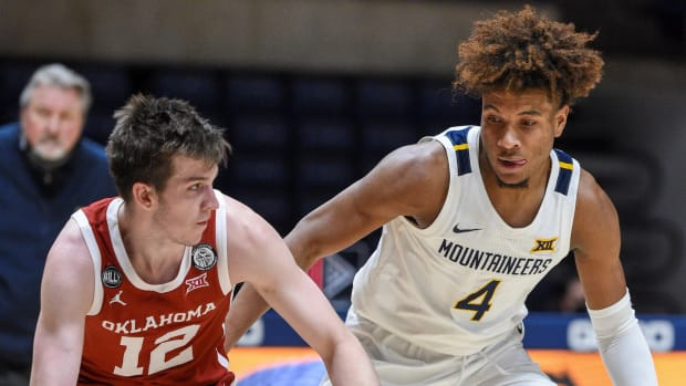 """West Virginia guard Miles """"Deuce"""" McBride (4) defends Oklahoma guard Austin Reeves (12) in the Sooners 91-90 double-overtime win over the Mountaineers."""